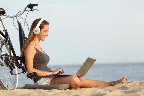 mulher com computador e headphones sentada na praia