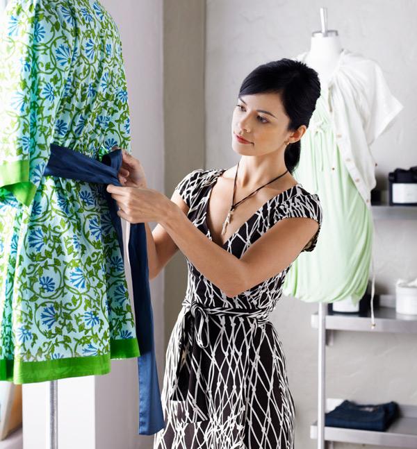 Decoradora a preparar um manequim na vitrina de uma loja.