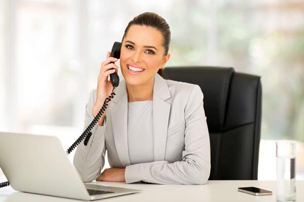 Assistente administrativa ao telefone a trabalhar num computador