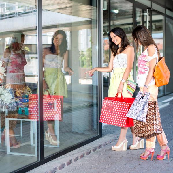 Duas potenciais clientes olham para a vitrina de uma loja