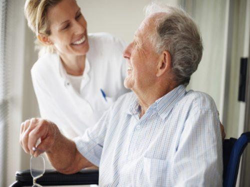 Idoso feliz a conversar com uma auxiliar de geriatria.
