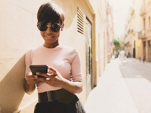 Rapariga mexe no telemóvel numa rua