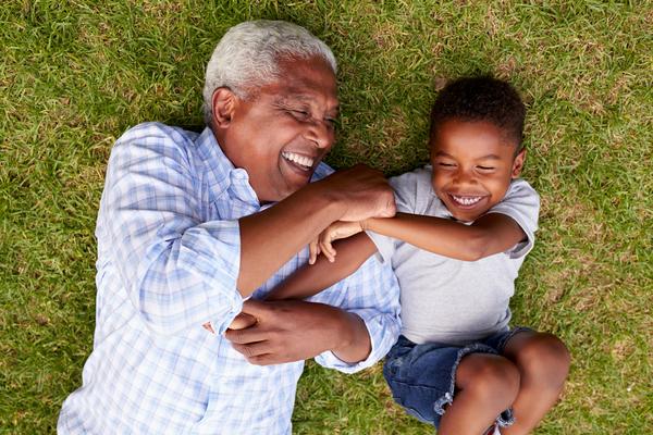Avó a brincar com  o neto na relva