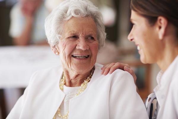 Idosa a falar com uma auxiliar de geriatria