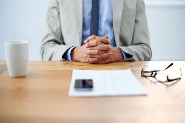 homem sentado num secretária com o seu curriculum à frente