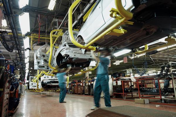 Linha de montagem com dois trabalhadores da indústria