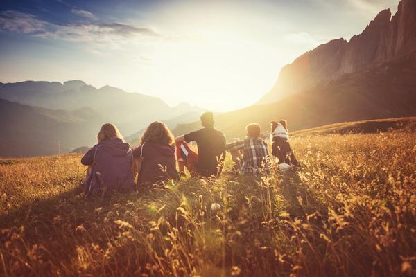 Grupo de amigos sentados no monte a ver o pôr-do-sol