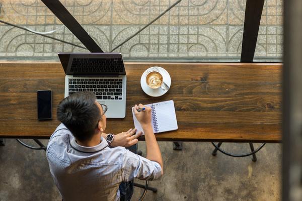 Rapaz que estuda numa esplanada através do campus virtual