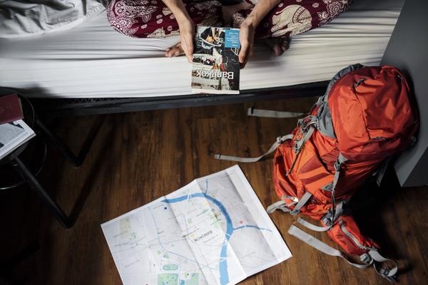 Pessoa sentada num quarto de hostel segurando um mapa