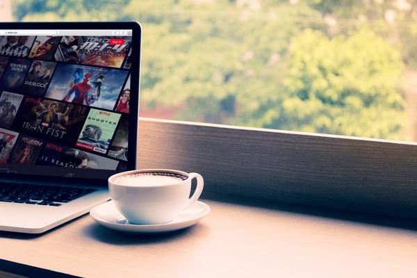 Computador portátil em cima de uma bancada com o site da netflix aberto.