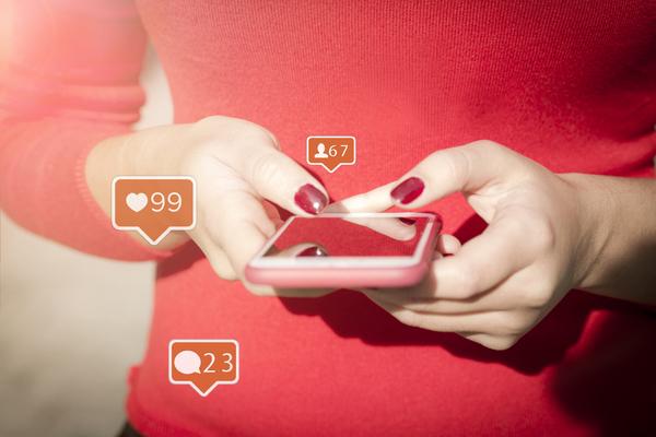 mulher a usar um smartphone e a receber likes, comentários e pedidos de amizade