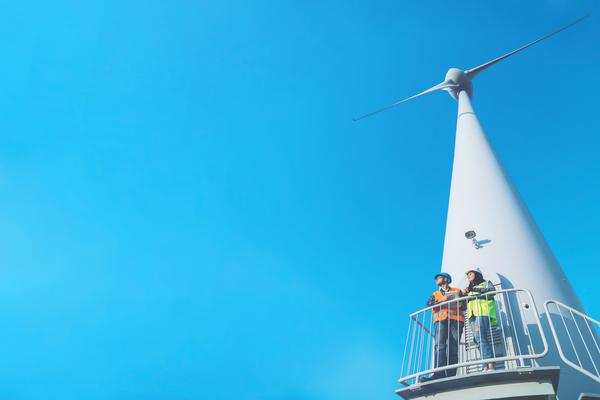 duas pessoas em cima de uma eólica, uma das fontes renováveis possíveis