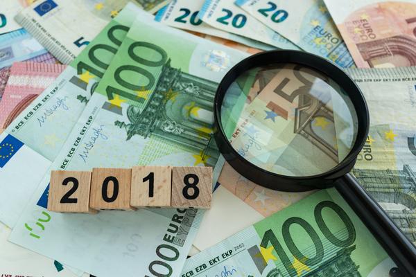 """notas de euro com uma lupa e blocos que formam """"2018"""""""